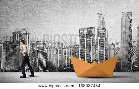Successful businessman pulling with rope paper boat