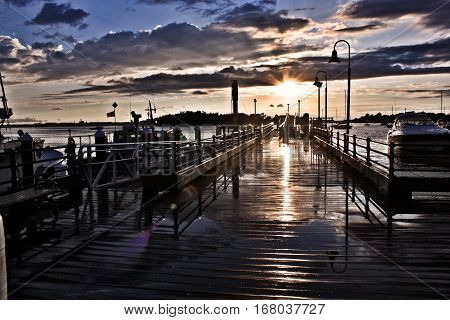 Wet Fishing Pier at Sunset. After a rain storm the  dark clouds are breaking to reveal an amazing setting sun as the colors bounce and reflect off the wet wooden pier.