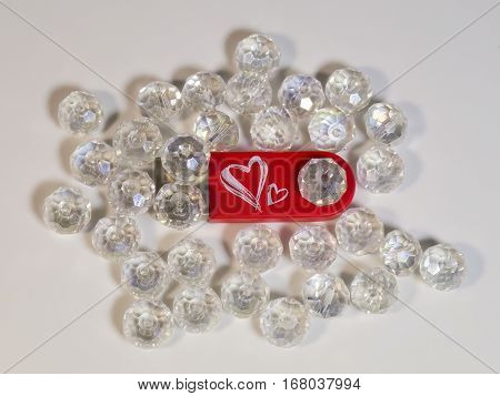 The red USB flash drive with heart and gems on light background