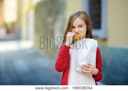 Adorable Little Girl Eating Fresh Baked Bun On Warm And Sunny Summer Day