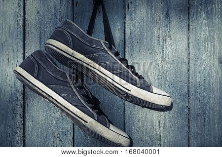 Blue textile torn sneakers hanging from a nail on a background of blue wooden wall