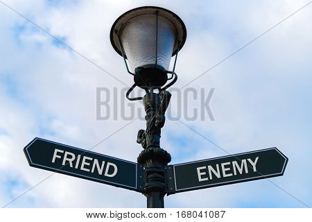 Friend Versus Enemy Directional Signs On Guidepost