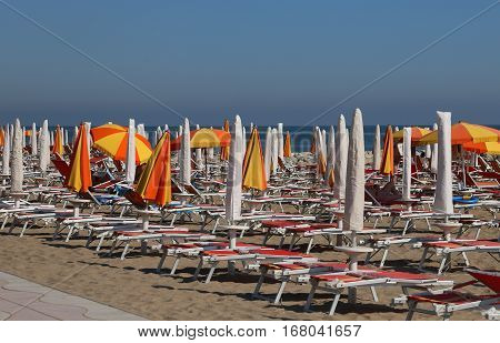Parasols And Deck Chairs In The Sun-drenched Beach In Summer