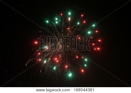 Red and Green Fireworks Burst into the Air against a black sky on New Years Eve 2016.