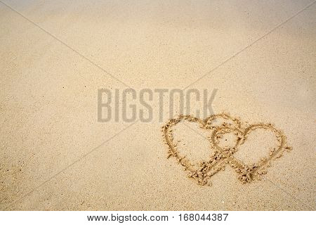 Two love hearts drawn on the caribbean beach.