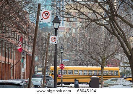 Typical Canadian street in winter under the snow in Toronto, Ontario, with parking street signs and a school bus