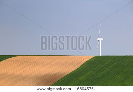 Wind turbinel on blue sky background. White wind power station in green field. Environmental protection concept. Background of no pollution energy.