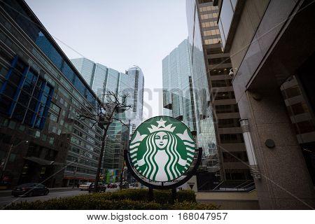 TORONTO, CANADA - DECEMBER 31, 2016: Starbucks logo in front of skyscrapers in Downtown Toronto, Ontario, Canada