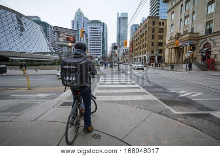 TORONTO, CANADA - DECEMBER 31, 2016: Uber Eats delivery man on a bicycle waiting to cross a street