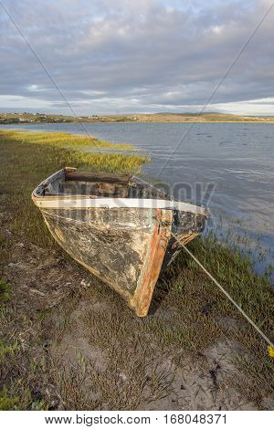 An old hull of a motorboat lies tied to the bank of a river as it is viewed from the front.