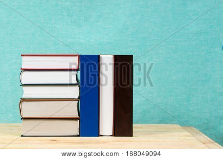 Stack of hardback books on wooden table. Back to school. Copy space.