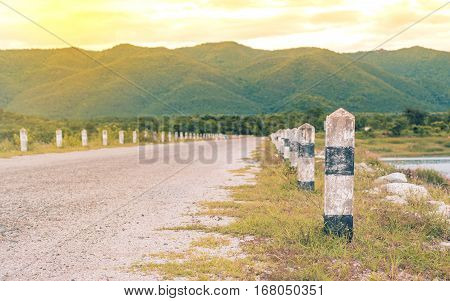 Road To Mountain With Concrete Barrier In Evening