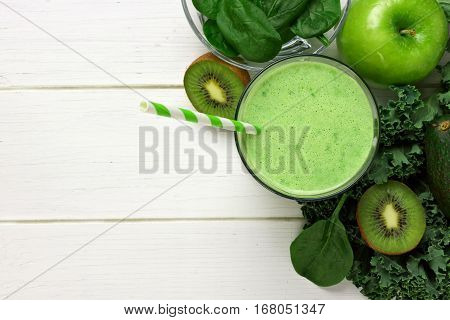 Green Smoothie Above View With Kale, Avocado, Spinach, Apple And Kiwi Against A White Wood Backgroun