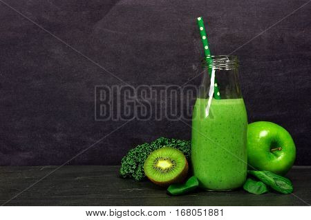Green Smoothie In A Milk Bottle With Kale, Spinach, Kiwi And Apple Against A Dark Slate Background