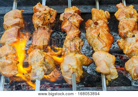 Marinated shashlik preparing on a barbecue grill over charcoal. Shashlik or Shish kebab popular in Eastern Europe. Shashlyk skewered meat was originally made of lamb. Roast Beef Kebabs On BBQ Grill.