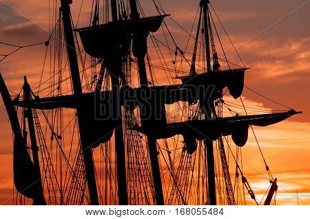 all ship masts and rigging silhouetted against a dramatic sky at sunset
