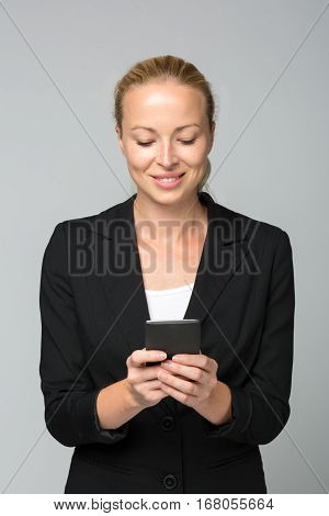 Beautiful young caucasian businesswoman in business attire using smart phone application. Studio portrait shot on gray background.
