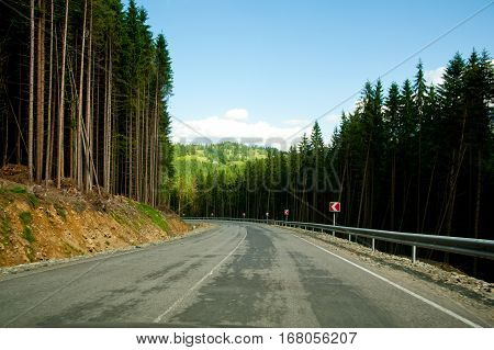 Empty curved road in mountains, blue sky