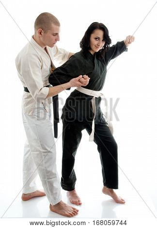 Karate. Man and girl in a kimono on the white background