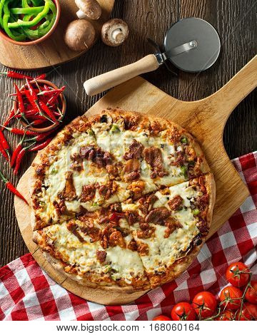 A delicious spicy pork pizza with green pepper onion and mushrooms.