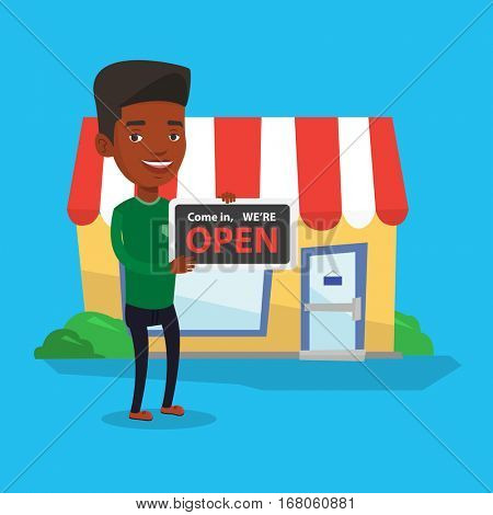 Friendly african-american shop owner holding open signboard. Cheerful shop owner standing in front of small store. Man inviting to come in his shop. Vector flat design illustration. Square layout.