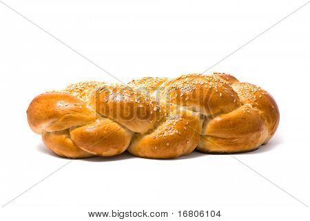 Single fresh bun and ear of wheat, soft shadow on white