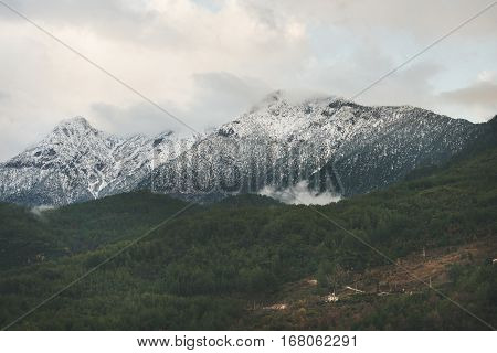 Green slopes of the Taurus mountains covered with snow in winter. Southern Turkey, Alanya, Dim Cay river valley