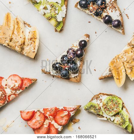 Healthy breakfast toast pieces. Wholegrain bread slices with cream cheese, various fruit, seeds and nuts. Top view, grey marble background, square crop. Clean eating, vegetarian, dieting concept