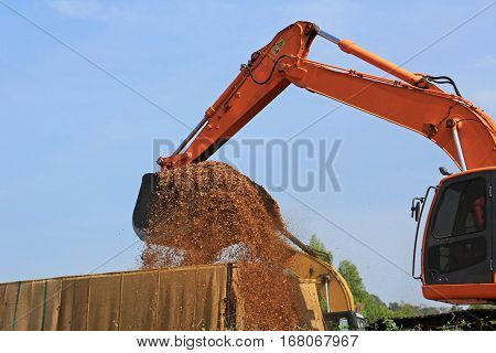 Backhoe Loading Wood Chips into a Truck