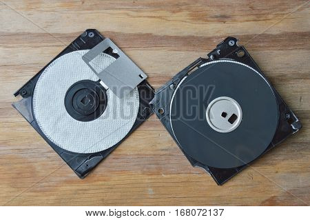 broken black diskette arranged on wooden board