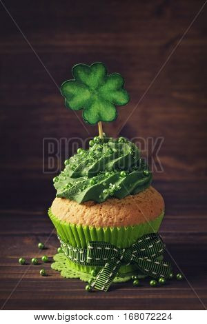 Cupcake with clover cakepick on a wooden background
