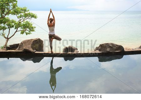 Woman practicing or doing morning meditation Yoga in nature at the beach