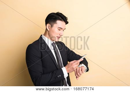 Asian business man use smart watch and phone, closeup portrait on studio yellow background