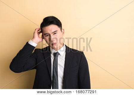 young Asian business man feel confused , closeup portrait on studio yellow background