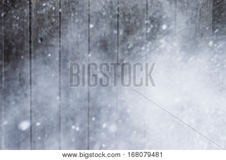 Strong storm and snow falling on the background of gray wooden boards.