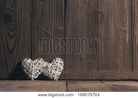 Two wicker hearts on brown wooden background