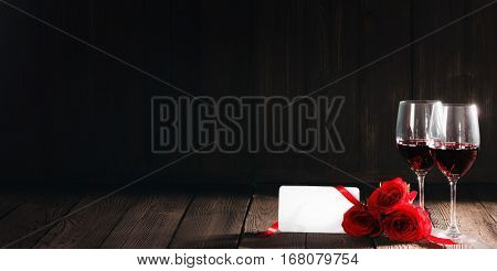 Two glasses of red wine, red roses and blank card on wooden background