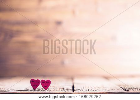 Two pink happy smiling hearts on wooden background