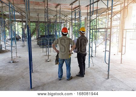 Construction concepts Engineer and Architect working at Construction Site with blueprint