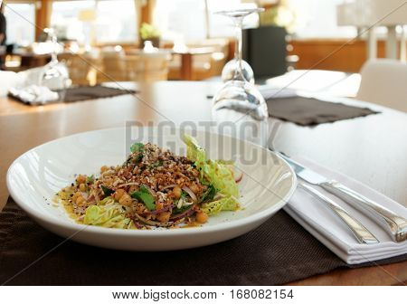 Raw vegan starter dish of nuts, salad and herbs on restaurant table