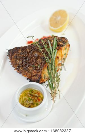 Grilled flounder with lemon, herbs and savory sauce on white plate