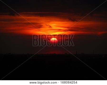 dark red sun at sunset over a black silhouette of Chicago