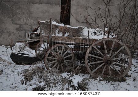 cart, wagon, dray, wain with big huge wooden wheels in snow in winter