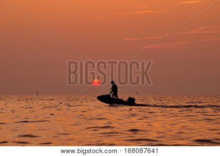 Silhouette of man driving jetski on the sea with during sunset