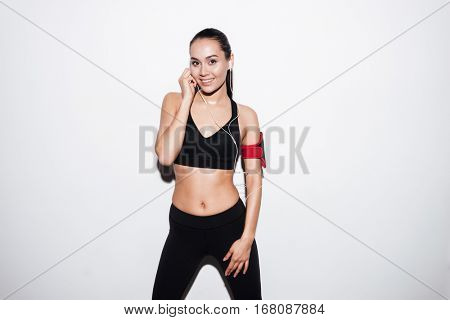 Happy charming young fitness woman with armband standing and listening to music over white background