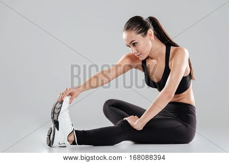 Pretty young sportswoman sitting and stretching legs over gray background