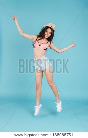Image of happy young lady with long hair wearing hat and dressed in swimwear jumping over blue background
