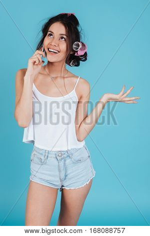 Picture of cheerful young lady with hair curlers isolated over blue background talking by phone