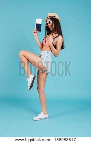 Image of pretty young lady with long hair wearing hat and dressed in swimwear posing over blue background holding passport and make winner gesture
