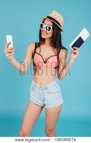 Picture of attractive young lady with long hair wearing hat and dressed in swimwear posing over blue background holding passport and make a selfie